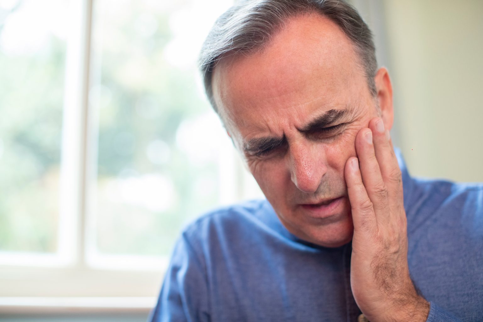 Mature Man Suffering With Toothache And Rubbing Painful Tooth